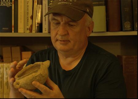 Father Eugen examines an archeological find at EBAF.