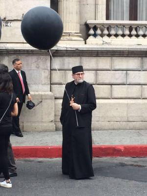 Archpriest Chad Hatfield, holding one of the black balloons representing a lost life, at the public commemoration.