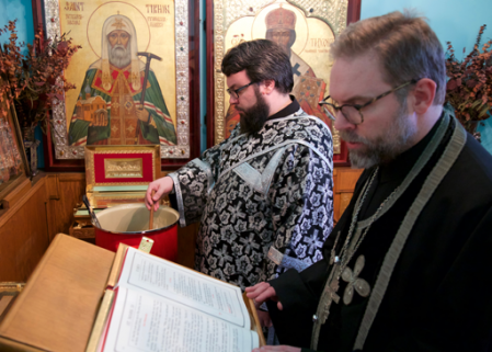 Seminarian Fr. Seth Earl reads the Holy Gospel while Seminarian Dn. Daniel Greeson stirs the special blend of oil and spices (photo: Dn. Evan Freeman)