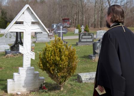 Fr. Alexander Rentel prays at the gravesite of Fr. Alexander and Mat. Juliana Schmemann (photo: Dn. Evan Freeman)