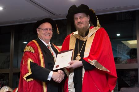 Dr. Graeme L. Blackman AO, conferring the degree upon Archpriest John Behr (photo: Andre White, University of Divinity)